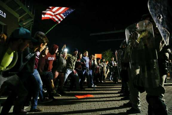 Students sing the Aggie War Hymn in front of riot police outside the Memorial Student Center as they protest white nationalist Richard Spencer speaking at Texas A&M University Tuesday, Dec. 6, 2016 in College Station.
