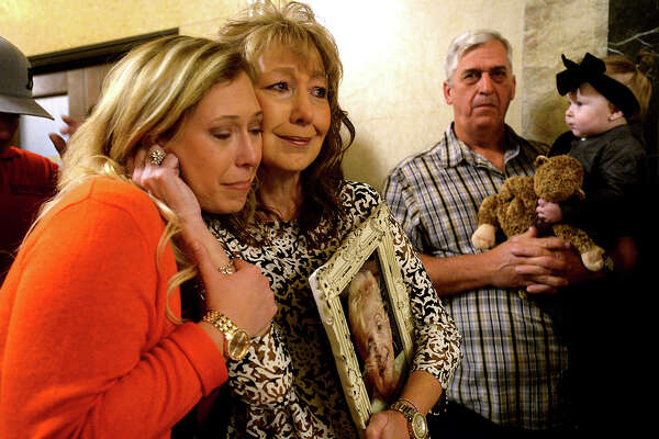 Kasidi Thibodeaux and her mother Teri Thibodeaux hug while consoling one another following a prayer during the Coalition for Victims of Violent Crime's annual Angel Tree ceremony Tuesday night at the Jefferson County Courthouse. The family attended the event for the first time to honor Robbie Allen, Teri's mother, who was a victim of homicide in December, 2011. Families who have lost loved ones to violence gathered to support one another as they remembered and paid tribute to those lost, hanging Christmas ornaments in their honor on the tree.  Photo taken Tuesday, December 6, 2016 Kim Brent/The Enterprise
