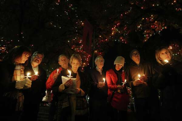 Valerie Redus (fourth from left) and her husband, Mickey (third from left), join others in a candlelight vigil to mark the three-year anniversary of the death of their son, Cameron, in front of the University of the Incarnate Word on Tuesday, Dec. 6, 2016. Cameron was a student at UIW who was shot five times by a campus police officer in 2013. The vigil was held the night before the Redus family attorney goes before State Supreme Court with arguments in the wrongful death suit filed by the Redus family. About 40 people gathered for the vigil - many who were Cameron's classmates.  (Kin Man Hui/San Antonio Express-News)