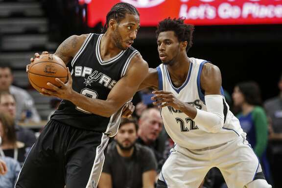 San Antonio Spurs forward Kawhi Leonard (2) works against Minnesota Timberwolves forward Andrew Wiggins (22) in the second half of an NBA basketball game, Tuesday, Dec. 6, 2016, in Minneapolis. The Spurs won 105-91. (AP Photo/Bruce Kluckhohn)
