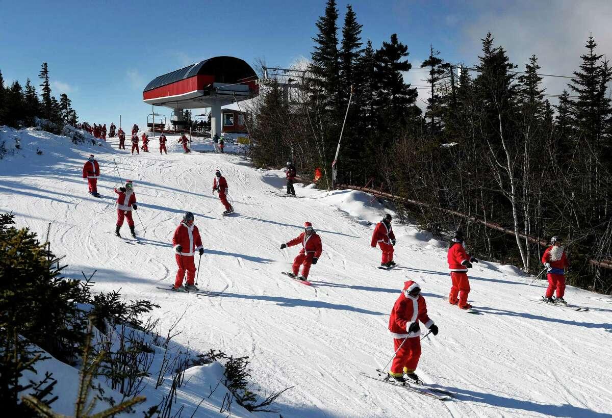 Skiers dressed as Santa Claus ski en masse, Sunday, Dec. 4, 2016, at the Sunday River ski resort in Newry, Maine. The annual Santa Sunday event raises money for local charities. (AP Photo/Robert F. Bukaty)