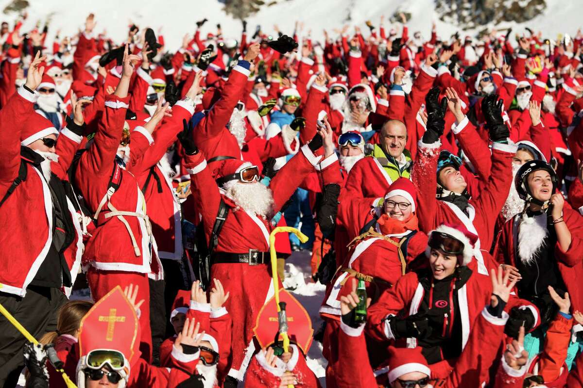 People dressed as Santa Claus pose for a group photo during a promotional event on the opening weekend in the alpine ski resort in Verbier, Switzerland, on Saturday, Dec 3, 2016. Around 1,200 skiers dressed as Santa Claus were granted free access to the ski resort to celebrates the ski season's opening. (Jean-Christophe Bott/Keystone via AP)