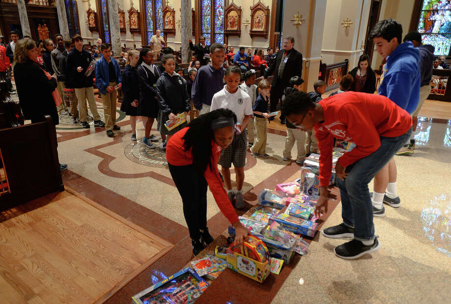 Students place toys at the St. Anthony Basilica alter to be blessed on Monday. After being blessed, the toys were donated to the Empty Stocking fund.  Photo taken Tuesday, December 2016 Guiseppe Barranco/The Enterprise Photo: Guiseppe Barranco, Photo Editor