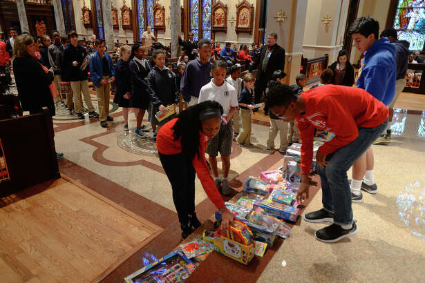 Students place toys at the St. Anthony Basilica alter to be blessed on Monday. After being blessed, the toys were donated to the Empty Stocking fund.  Photo taken Tuesday, December 2016 Guiseppe Barranco/The Enterprise