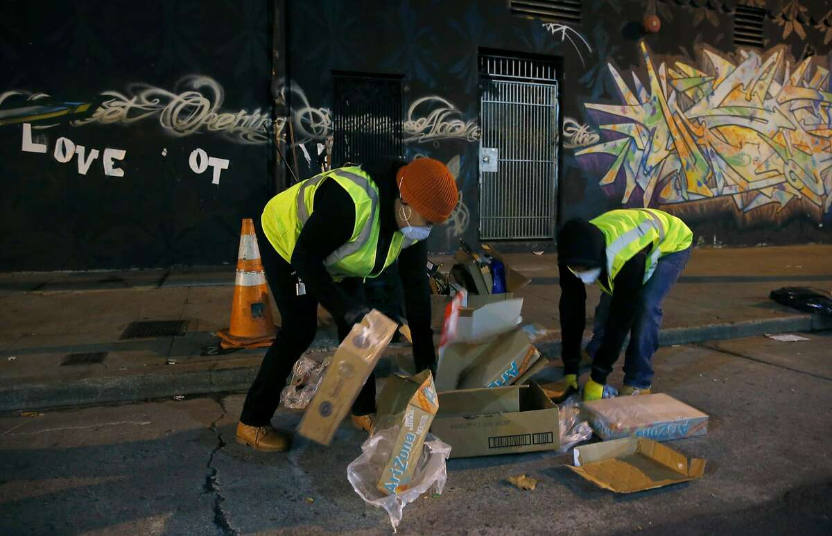 Sammisha Hicks (left) and Chaz Cobb with the TL Cares clean team pick up trash on Turk Street in the Tenderloin for the Department of Public Works in San Francisco, Calif. on Wednesday, Dec. 7, 2016.