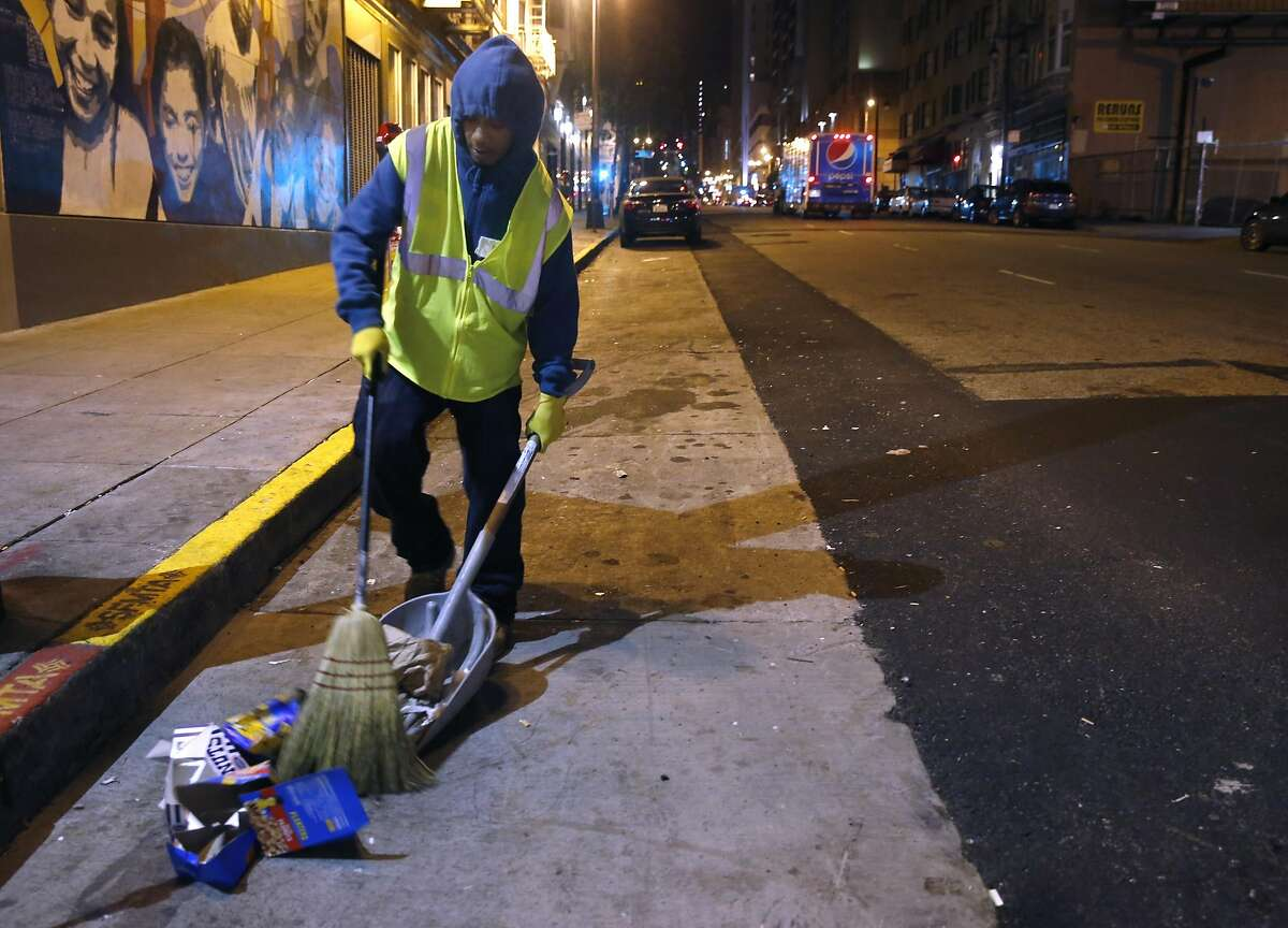 Tyrone Corley with the TL Cares clean team sweeps trash from Taylor Street in the Tenderloin for the Department of Public Works in San Francisco, Calif. on Wednesday, Dec. 7, 2016.