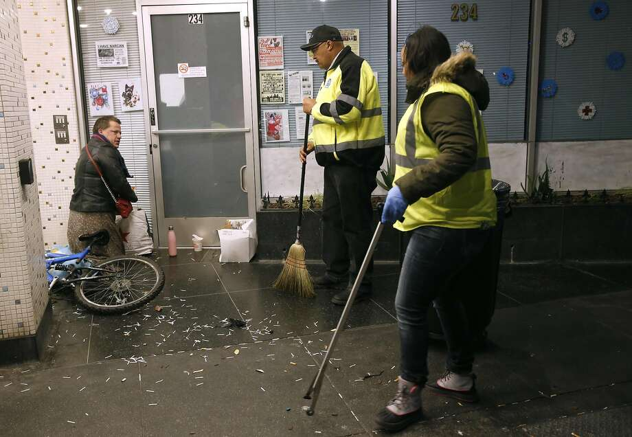 Director of Public Works Mohammed Nuru (center) tells a man sleeping in a doorway to move on so his department's TL Cares clean team can pick up trash in the Tenderloin in San Francisco, Calif. on Wednesday, Dec. 7, 2016. Photo: Paul Chinn, The Chronicle