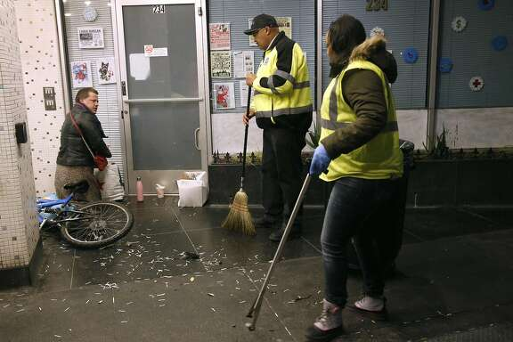 Director of Public Works Mohammed Nuru (center) tells a man sleeping in a doorway to move on so his department's TL Cares clean team can pick up trash in the Tenderloin in San Francisco, Calif. on Wednesday, Dec. 7, 2016.