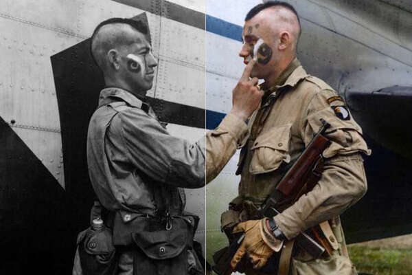 Filthy Thirteen member Clarence Ware applies war paint to Charles Plaudo. England, December 31, 1943.