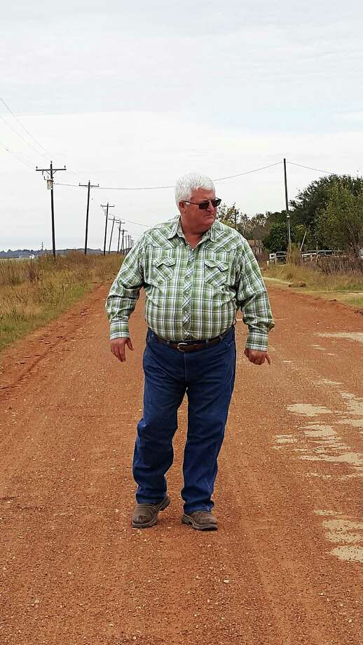Pct. 3 Commissioner-elect 'Boo' Reaves looks over one of the roads near Dayton that he will inherit. Heavy farm equipment damages the roads and makes them almost impassable for school buses picking up and delivering children home or to the school. Photo: David Taylor