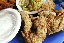 Two-piece fried chicken lunch with sides of mac and cheese and onion rings from Radicke's Bluebonnet Grill.