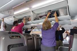 Australia, Melbourne Tullamarine Airport MEL Qantas airlines onboard flight cabin business class passengers disembarking overhead luggage bins removing woman reaching. (Photo by: Jeff Greenberg/UIG via Getty Images)
