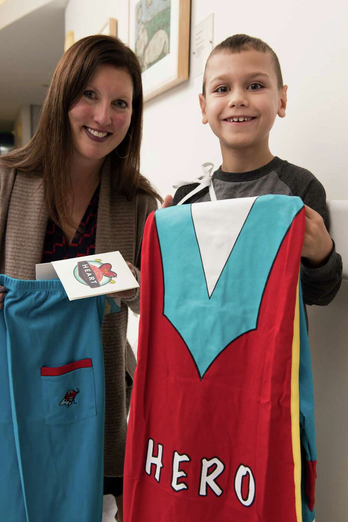 Holly Hancock, an adult congenital heart disease patient, presents hero pajamas to a young patient at Texas Children's.
