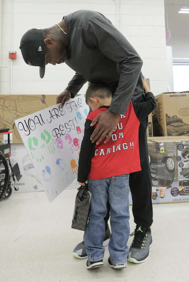 Former Texan Andre Johnson gets a hug and a sign from Towlyn Dominguez, 5, before a shopping spree at Toys R Us  on  Wednesday, Dec. 7, 2016, in Houston. With the help of the Texan cheerleaders, each child had 80 seconds (in honor of Johnson's jersey number) to grab as much as they can. Johnson's total shopping bill this year was $19144.58. Photo: Elizabeth Conley, Houston Chronicle / © 2016 Houston Chronicle