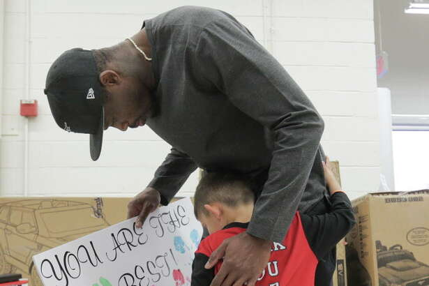 Former Texan Andre Johnson gets a hug and a sign from Towlyn Dominguez, 5, before a shopping spree at Toys R Us  on  Wednesday, Dec. 7, 2016, in Houston. With the help of the Texan cheerleaders, each child had 80 seconds (in honor of Johnson's jersey number) to grab as much as they can. Johnson's total shopping bill this year was $19144.58.