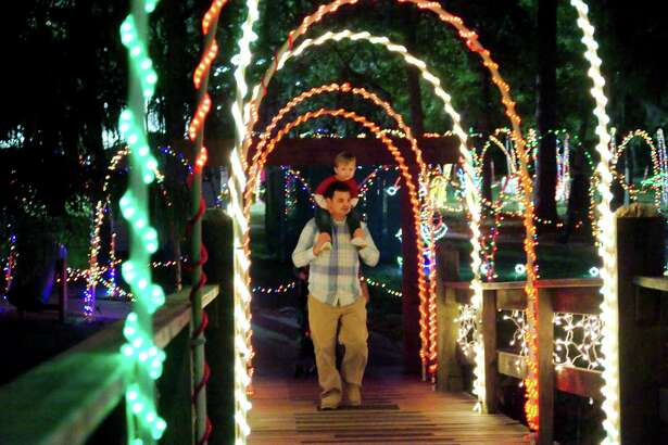 Zach Sparks and his son Preston enjoy the lights as they stroll across a bridge at the Dickinson Festival of Lights.