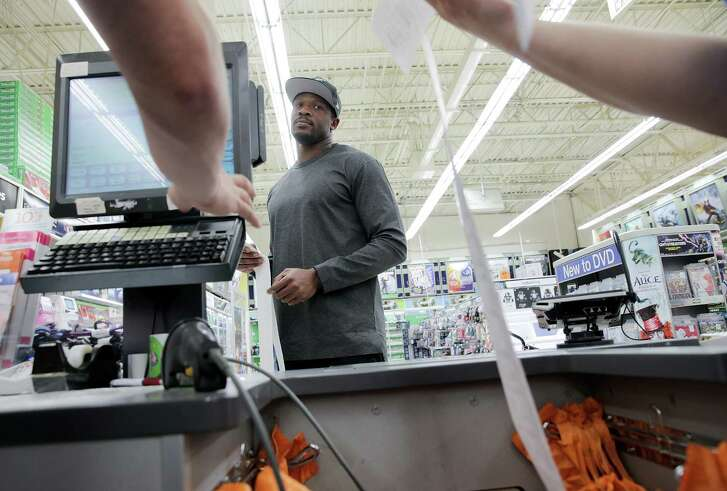 Former Texan Andre Johnson watches as the recipe tape spits out his final bill after  a holiday shopping spree for 12 children in Harris County's Dept. of Family Protective Services at Toys R Us on  Wednesday, Dec. 7, 2016, in Houston. Johnson's total shopping bill this year was $19144.58.