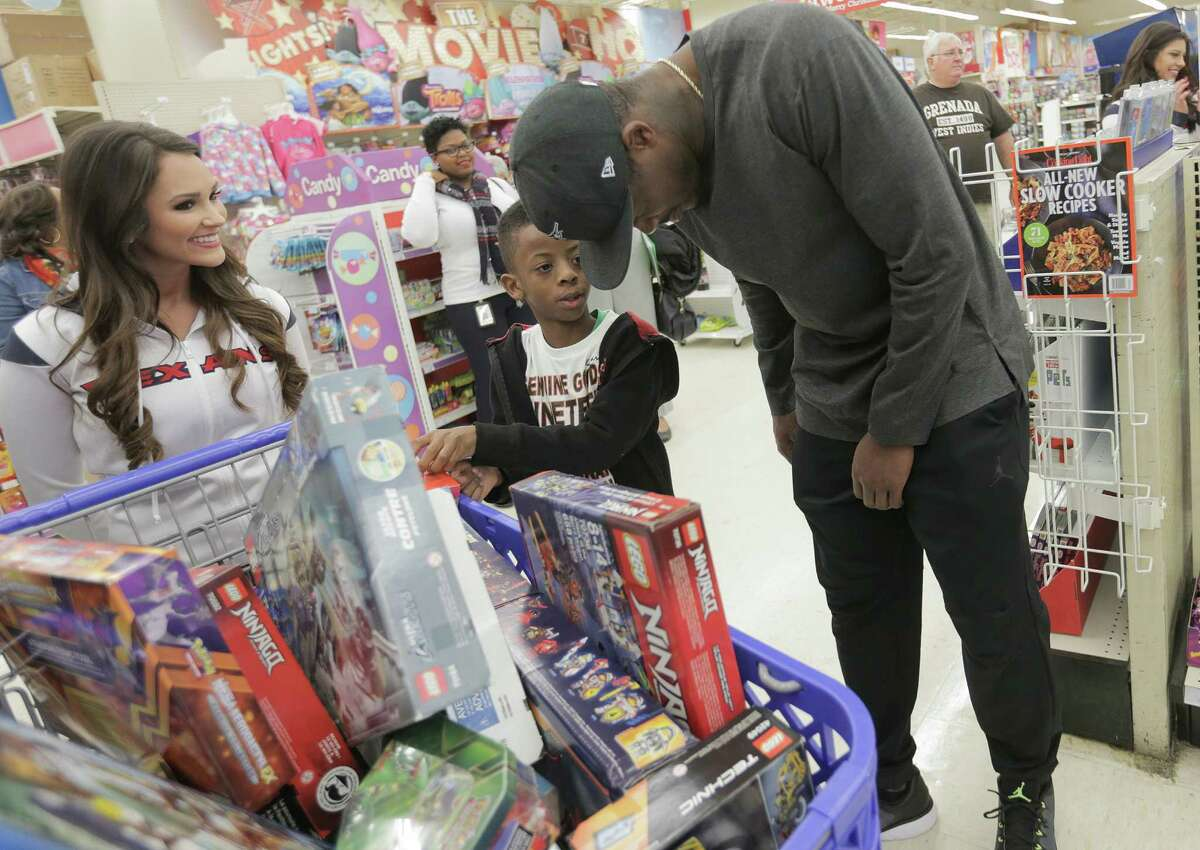 Former Texan Andre Johnson chats with Deleon Jackson, 8, about his lego sets he picked up. Jackson was going to give some to his brother. With the help of the Texan cheerleaders, each child had 80 seconds (in honor of Johnson's jersey number) to grab as much as they can. Johnson's total shopping bill this year was $19144.58.