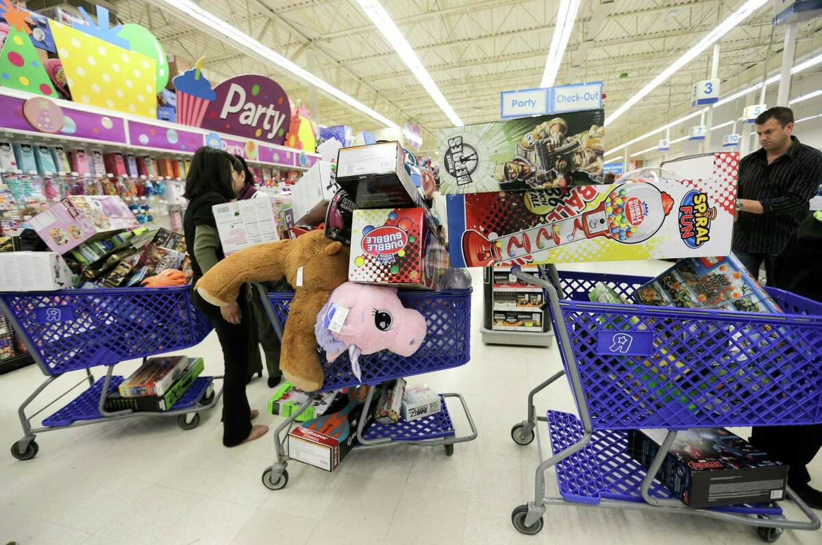 Filled shopping carts wait for an open aisle after a shopping spree sponsored by former Texan Andre Johnson at Toys R Us on Wednesday, Dec. 7, 2016, in Houston. With the help of the Texan cheerleaders, each child had 80 seconds (in honor of Johnson's jersey number) to grab as much as they can. Johnson's total shopping bill this year was $19144.58.