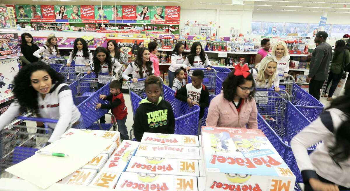 Children and Texan Cheerleaders start dashing through Toys R Us for an 80 second shopping spree sponsored by former Texan Andre Johnson on Wednesday, Dec. 7, 2016, in Houston. With the help of the Texan cheerleaders, each child had 80 seconds (in honor of Johnson's jersey number) to grab as much as they can. Johnson's total shopping bill this year was $19144.58.