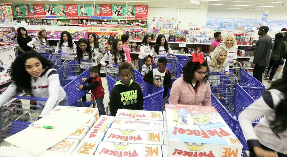 Children and Texan Cheerleaders start dashing through Toys R Us for an 80 second shopping spree sponsored by  former Texan Andre Johnson on Wednesday, Dec. 7, 2016, in Houston. With the help of the Texan cheerleaders, each child had 80 seconds (in honor of Johnson's jersey number) to grab as much as they can. Johnson's total shopping bill this year was $19144.58. Photo: Elizabeth Conley, Houston Chronicle / © 2016 Houston Chronicle
