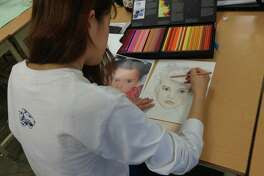 A Westbury Christian School art student works on the Memory Project.