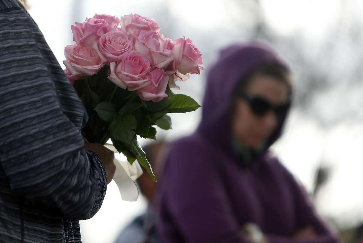Amy Ferrara of Berkeley holds flowers as Tiffany Snow of Oakland looks at a Fruitvale Avenue memorial as they remember their friend Griffin Madden who died in the Ghost Ship warehouse fire in Oakland, Calif., on Tuesday, December 6, 2016.