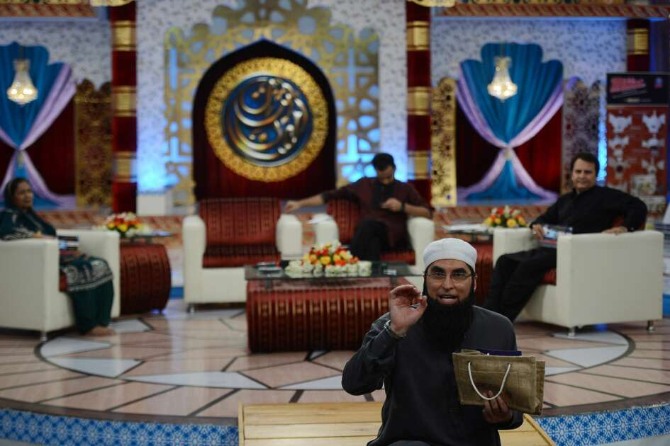 TO GO WITH Pakistan-religion-media-Islam,FOCUS by Guillaume Lavallee  In this photograph taken on August 1, 2013 Pakistani television show host Junaid Jamsheed presents an Islamic quiz show Shan-e-Ramadan in Karachi.  In the battle for TV ratings, Pakistan's top channels are making money out of Ramadan by broadcasting round-the-clock chat shows mixing prizes, charity and prayer.   AFP PHOTO / ASIF HASSAN        (Photo credit should read ASIF HASSAN/AFP/Getty Images)