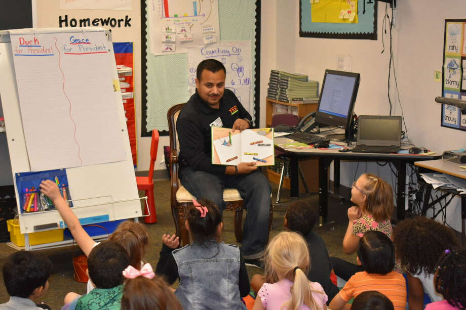 Juan Rodriguez of YES Youth Fitness and Sports Performance,  reads to pupils at Morton Ranch Elementary School as part of the annual Promise to Read in the Katy ISD. Photo: Katy ISD