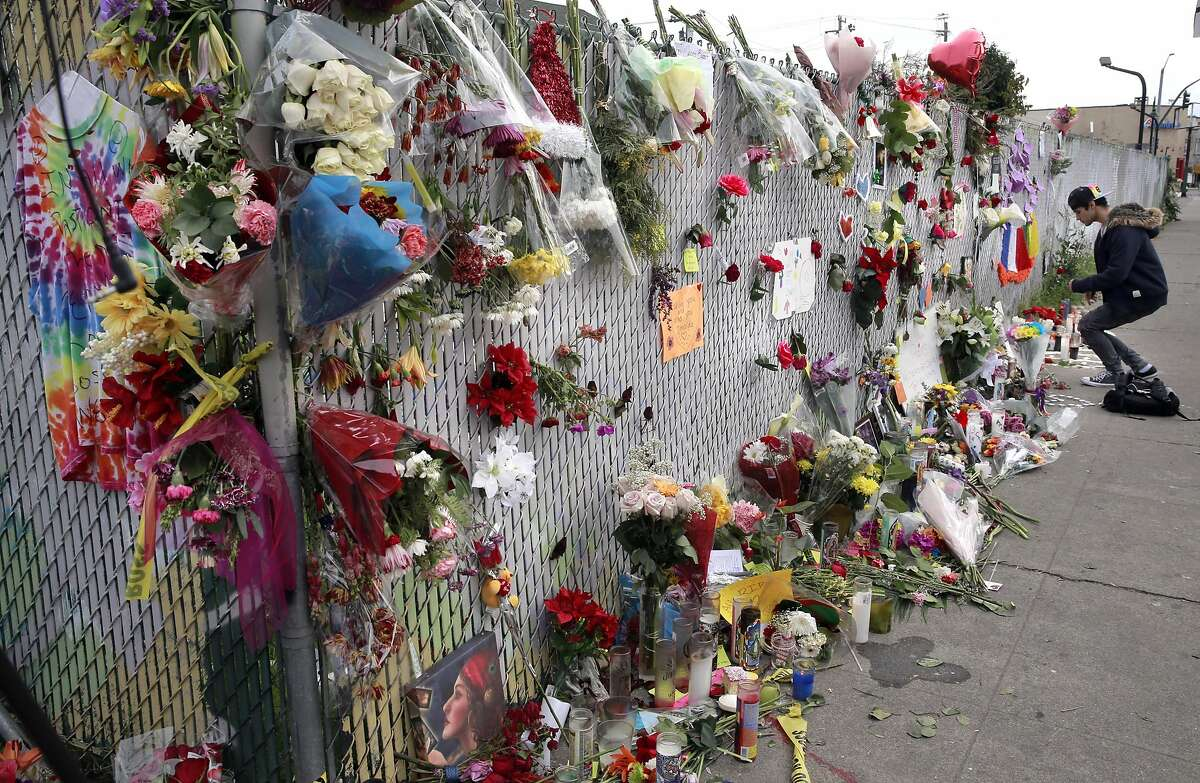 Saul Melgoza of Brentwood left flowers at a memorial along E. 12th street near the site of the ghost ship warehouse fire in Oakland, California, on Wednesday December 7, 2016,