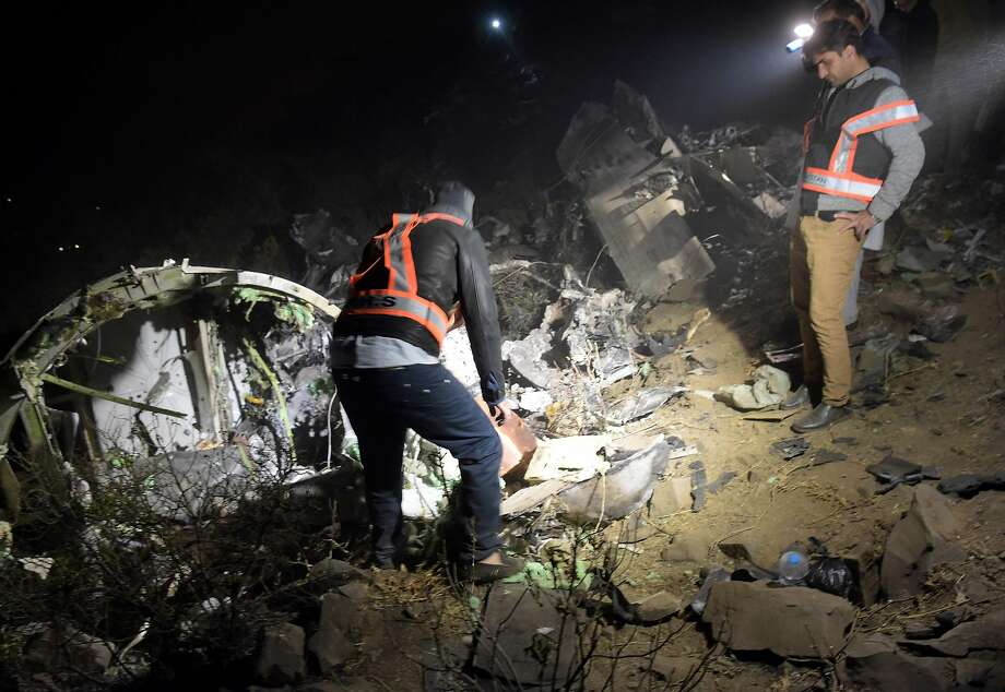"Pakistani officials of Pakistan International Airlines (PIA) looks at the wreckage of the crashed PIA passenger plane Flight PK661 at the site in the village of Saddha Batolni in the Abbottabad district of Khyber Pakhtunkhwa province on December 7, 2016. All 48 people on board a Pakistani plane which crashed in the country's mountainous north and burst into flames have died, officials told AFP on December 7, 2016. ""No one survived,"" said the Civil Aviation Authority spokesman.  / AFP PHOTO / AAMIR QURESHIAAMIR QURESHI/AFP/Getty Images Photo: AAMIR QURESHI, AFP/Getty Images"