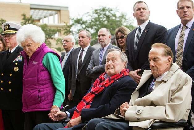 Former First Lady Barbara Bush, left, holds hands with her husband, former President George H.W. Bush and Sen. Bob Dole, R-Kansas, during the playing of Taps at the 75th anniversary ceremony of the attack on Pearl Harbor at the George Bush Presidential Library on Wednesday, Dec. 7, 2016, in College Station. Photo: Brett Coomer, Houston Chronicle / © 2016 Houston Chronicle