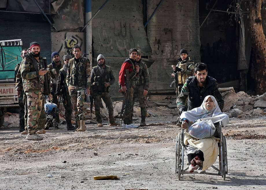 A member of the government forces pushes an injured woman in a wheelchair as civilians are evacuated from Aleppo's al-Shaar neighborhood after President Bashar Assad's forces took control of the area. Photo: GEORGE OURFALIAN, AFP/Getty Images