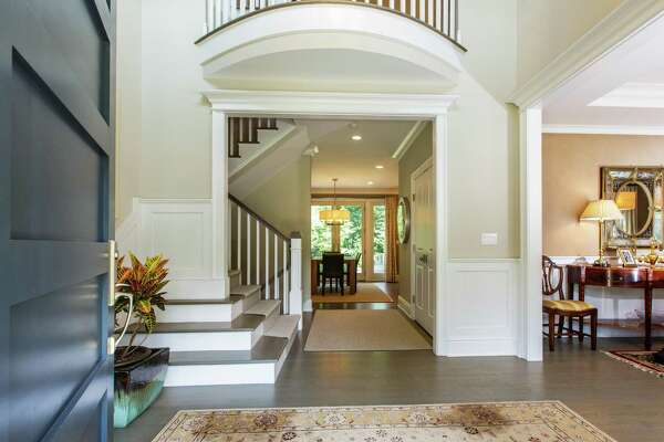 The two-story foyer of the colonial house at 5 Twin Circle Drive features an interior Juliet balcony, built-in bench and a formal powder room with a marble floor.