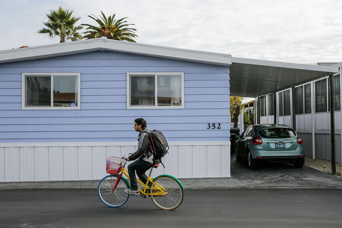 A man uses a Google bike to bike through the grounds of a mobile home park, in Mountain View, California, on Wednesday, Dec. 7, 2016.