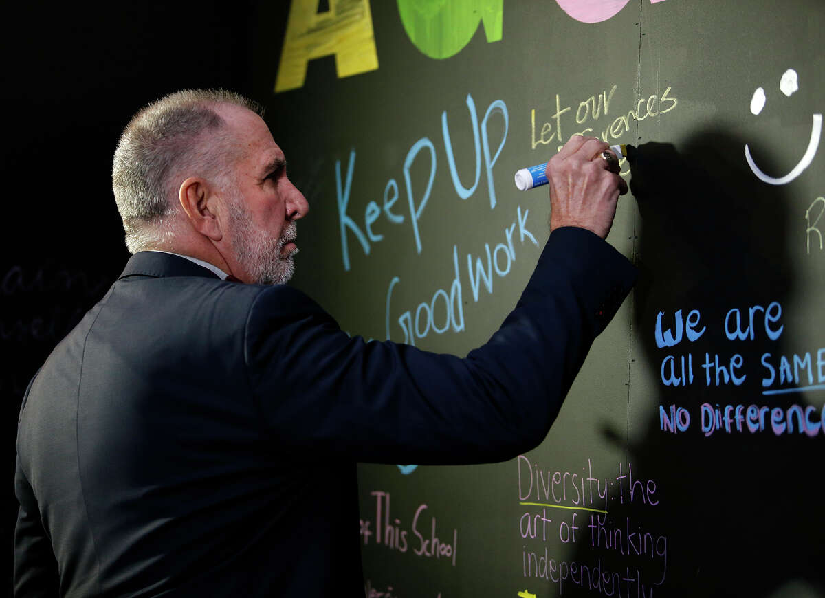 """Texas A&M President Michael Young signs a message board outside Kyle Field where an """"Aggies United"""" event is scheduled for Tuesday evening at the university Tuesday, Dec. 6, 2016, in College Station, Texas. The event is taking place at the same time Richard Spencer, who leads a movement that mixes racism, white nationalism and populism, is set to speak at a separate event at the university after being invited by a former student. (Stephen Spillman/Austin American-Statesman via AP)"""