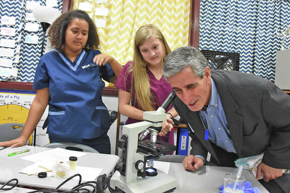 School Priority Day visitor Jeff Newman peeks through a microscope during his tour of a veterinary medicine classroom at Cy-Fair High School on Nov. 14.