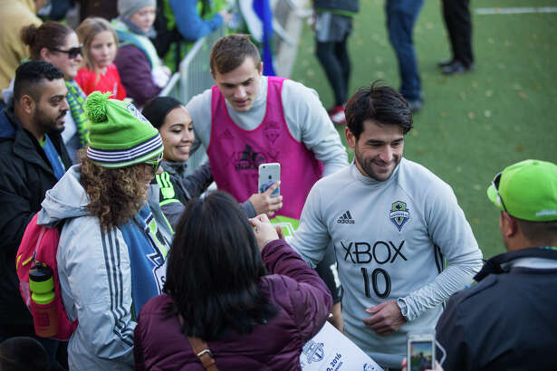 Sounders midfielder Nicol‡s Lodeiro and forward Jordan Morris greet fans as they head to the locker room after practice in Tukwila on Wednesday, Dec. 7, 2016. Fans gathered to show their support before the team heads to Toronto for the MLS Cup final.