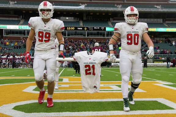 The Woodlands football players Michael Purcell, left, and Zachary Loane carry the jersey of linebacker Grant Milton, who was named an honorary captain before Saturday's playoff game at McLane Stadium in Waco. Milton suffered a serious head injury during the team's Nov. 26 victory. Across the top, Sebastian Garcia wears Milton's No. 21 in face paint, while signs of support from both foe (Round Rock) and friend (The Woodlands) dot the stadium.