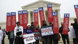 File photo of protesters holding signs with estimates of the numbers who could lose health insurance in each state if the verdict of King v. Burwell went against the Affordable Care Act, outside the Supreme Court in Washington, March 4, 2015. The Republican plan to delay repealing the ACA could cause a zombie market, not dead, but not alive, that would suffer from many of the maladies of the existing system, and quite a few more.