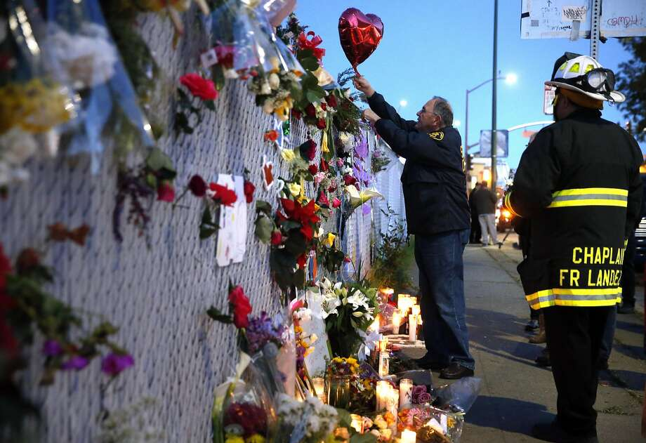 Alameda County Sherrif's chaplain, Ed Moore, center, attached a balloon to a memorial on E. 12th Street as Oakland Fire Department Chaplain Fr. Jayson Landez watches, right, as recovery efforts came to a close following the Ghost Ship fire that claimed 36 lives in Oakland, Calif., on Tuesday, December 6, 2016. Photo: Carlos Avila Gonzalez, The Chronicle