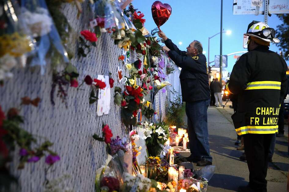 Alameda County Sherrif's chaplain, Ed Moore, center, attached a balloon to a memorial on E. 12th Street as Oakland Fire Department Chaplain Fr. Jayson Landez watches, right, as recovery efforts came to a close following the Ghost Ship fire that claimed 36 lives in Oakland, Calif., on Tuesday, December 6, 2016.