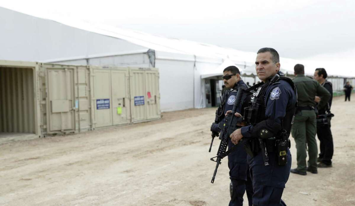 U.S. Customs and Border Protection agents stand outside a U.S. Customs and Border Protection temporary holding facility under construction near the Donna-Rio Bravo International Bridge, Wednesday, Dec. 7, 2016, in Donna, Texas. The tent facility, primarily to be used as a temporary holding site for children and families who have entered the county illegally, is due to open Friday and process up to 500 people a day. (AP Photo/Eric Gay)
