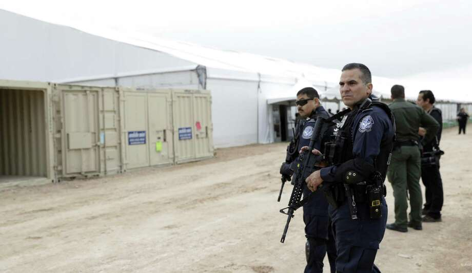 U.S. Customs and Border Protection agents stand outside a U.S. Customs and Border Protection temporary holding facility under construction near the Donna-Rio Bravo International Bridge, Wednesday, Dec. 7, 2016, in Donna, Texas. The tent facility, primarily to be used as a temporary holding site for children and families who have entered the county illegally, is due to open Friday and process up to 500 people a day. (AP Photo/Eric Gay) Photo: Eric Gay, STF / Associated Press / Copyright 2016 The Associated Press. All rights reserved.