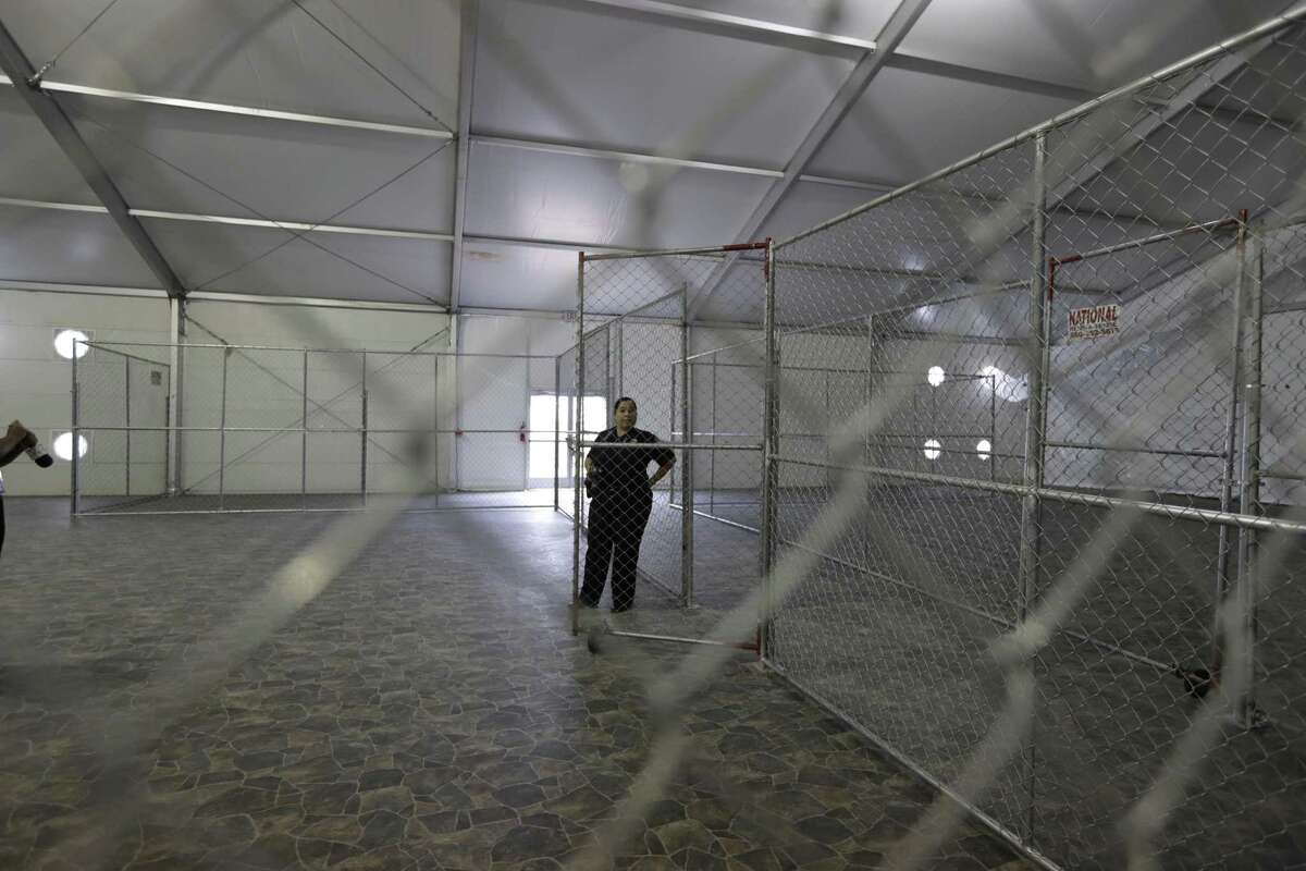 A Customs and Border Protection agent stands in a temporary holding facility near the Donna-Rio Bravo International Bridge.