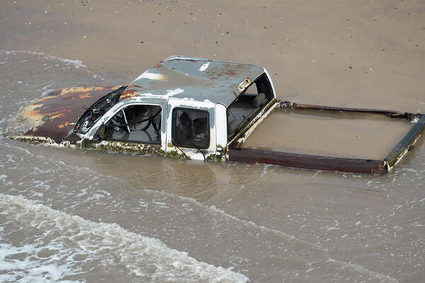 A rusted car stuck in the surf between Sabine Pass and Bolivar Peninsula. Photo taken Friday, July 15, 2016 Guiseppe Barranco/The Enterprise