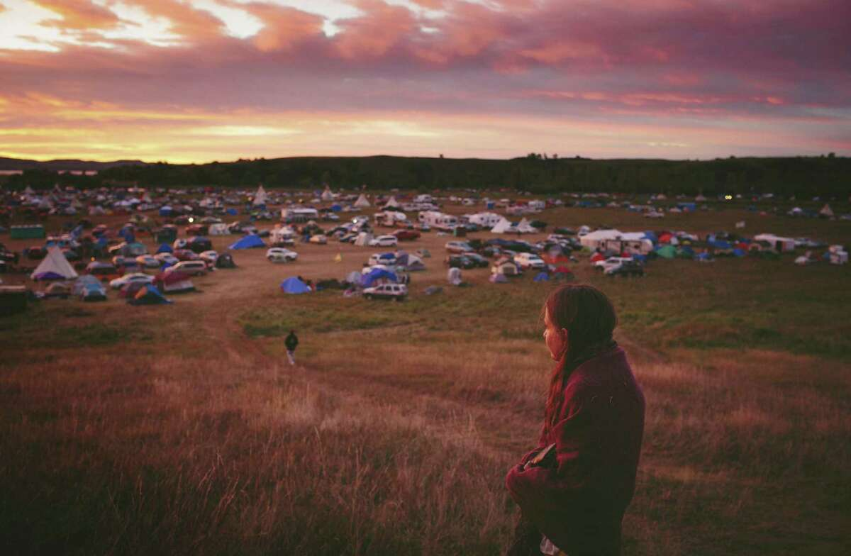 Susan Leopold of the Patawomeck Tribe of Virginia, watches the sun rise over the Sacred Stone Camp, where thousands of Native Americans have joined the Standing Rock Sioux tribe?'s protest against an oil pipeline, in Cannon Ball, N.D., Sept. 9, 2016. Ranchers and residents in the conservative, overwhelmingly white countryside view the demonstrations with a mix of frustration and fear, reflecting the deep cultural divides and racial attitudes. (Alyssa Schukar/The New York Times)