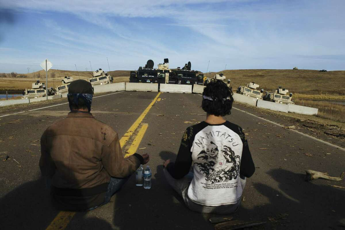 Police face off against protestors occupying a bridge immediately north of the Standing Rock Sioux Reservation in Cannon Ball, N.D., Oct. 28, 2016. A day after tensions boiled over here in a conflict over the fate of the Dakota Access pipeline, police officers said Friday they had arrested at least 141 protesters, and both sides complained about violent tactics used by the other. (Angus Mordant/The New York Times)
