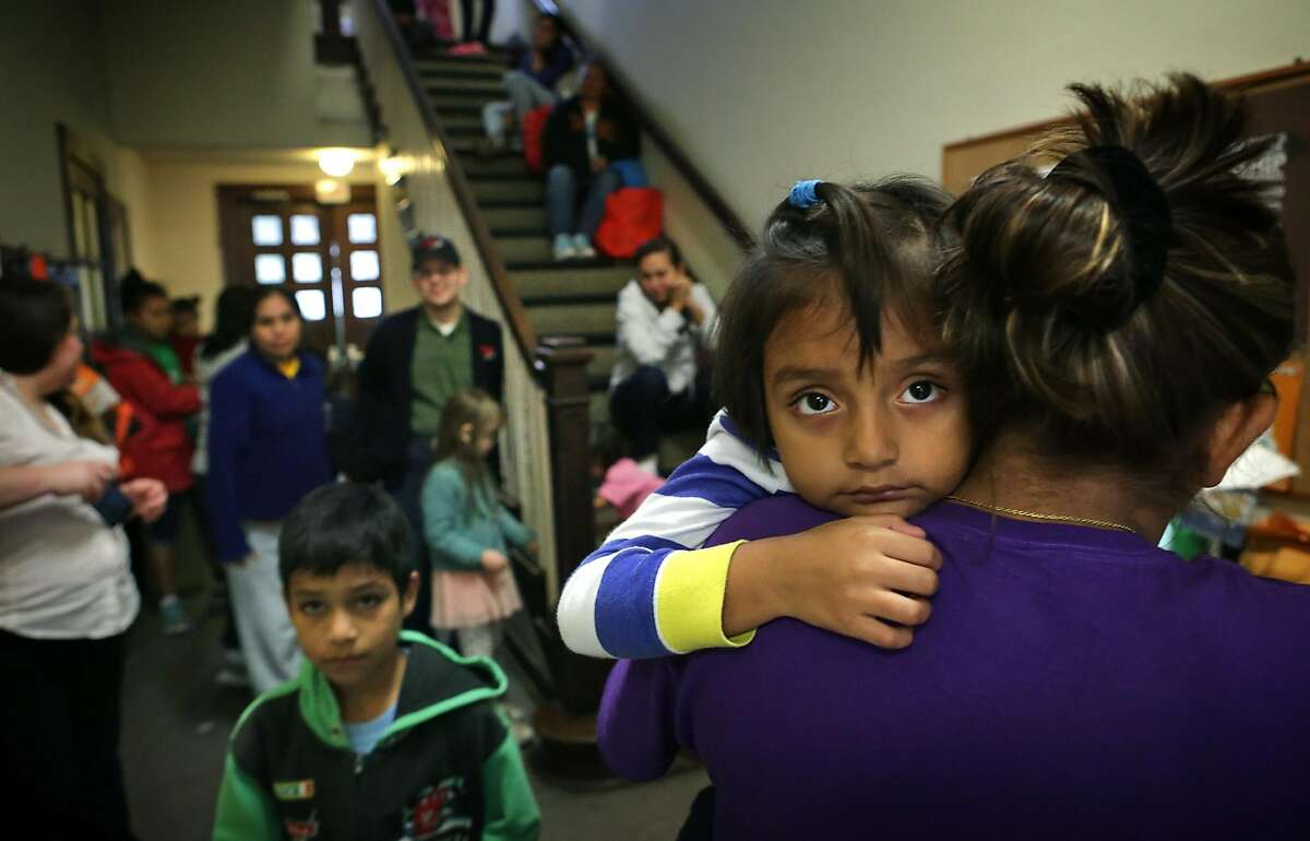 Ashley Rivas, 4, looks over the shoulder of her mother Griselda Rivas, 30, of El Salvador, after arriving at the San Antonio Mennonite Church where hundreds of immigrants from Central America have been dropped off by ICE. Volunteers mentioned they went out to buy blankets and air mattresses, and the last bus dropped off another group at 3 A.M. on Monday, Dec. 5, 2016.