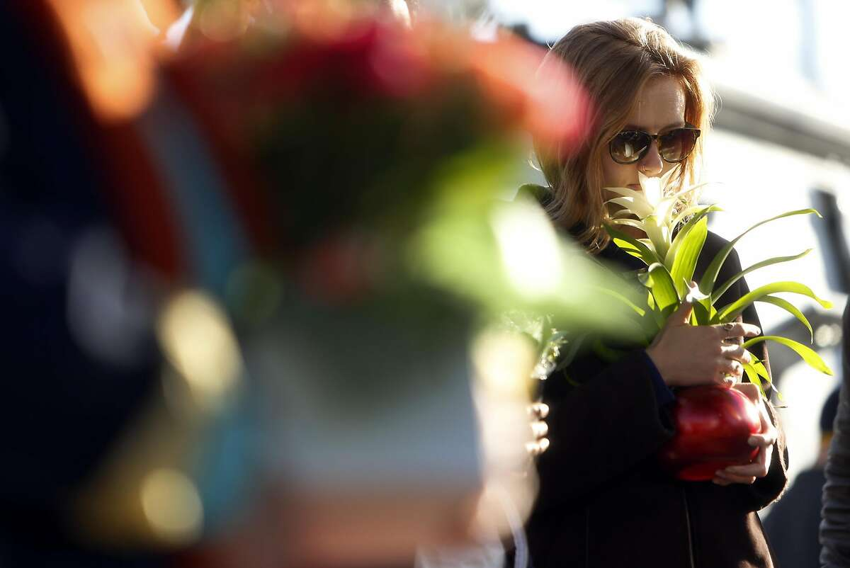 Genevieve Krause of Oakland pauses at memorial before placing a flower in the aftermath of the deadly Ghost Ship warehouse fire in Oakland, Calif., on Tuesday, December 6, 2016.